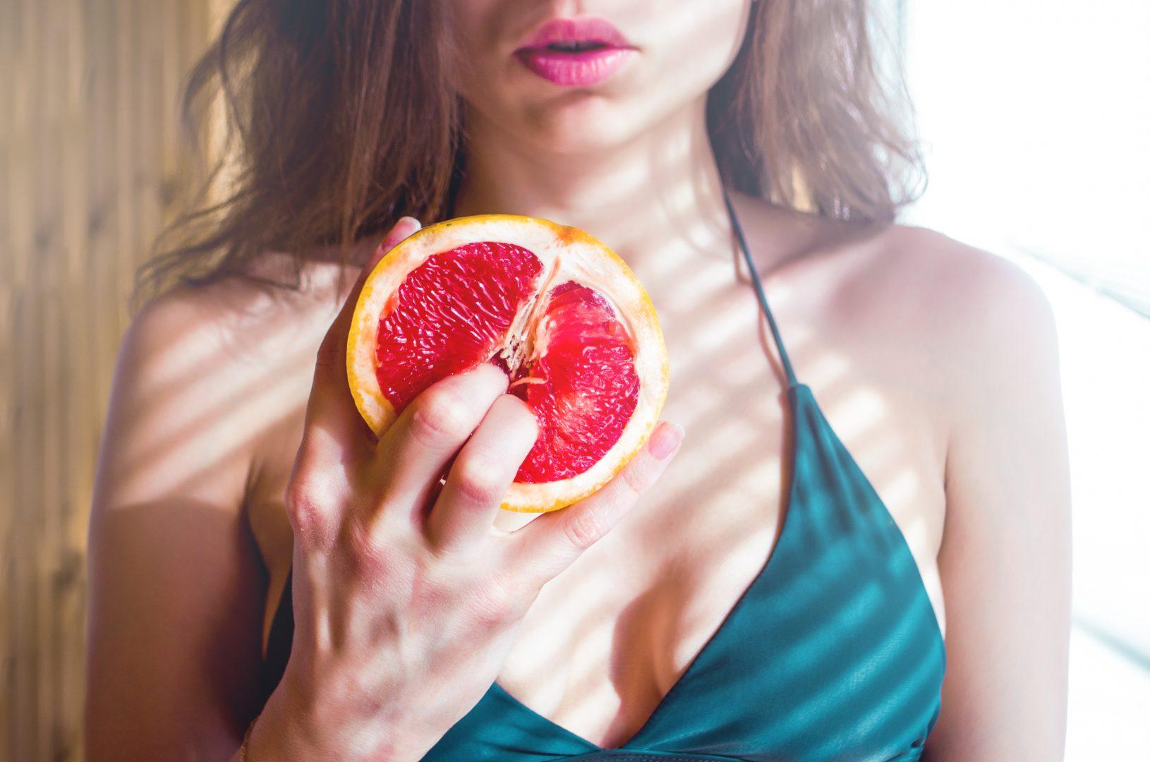 Oralsex - bilde av kvinne som stikker fingrene inn i en grapefrukt.