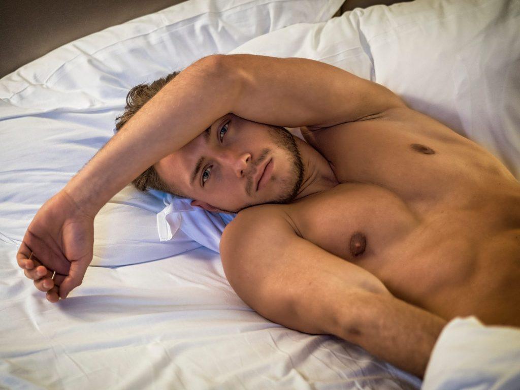 Blond veltrent halvnaken mann i sengen.