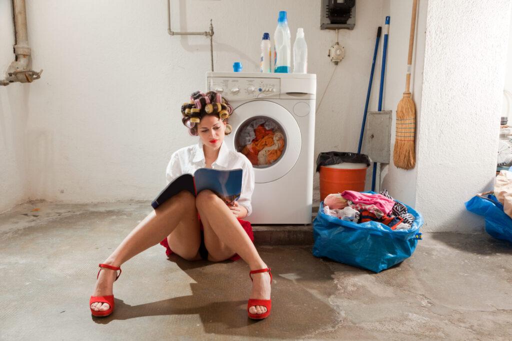 En dame med rødt undertøy og hårruller sitter på gulvet i en vaskekjeller og leser.